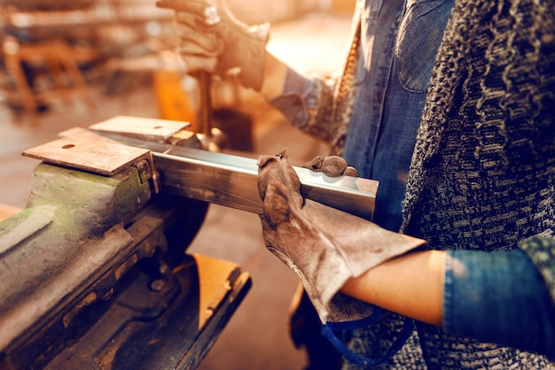 Trabalhadora coloca a haste de metal no espremedor usando luvas de proteção.