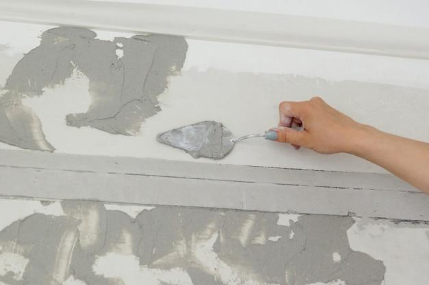 Trabalhadora coloca solução de massa na parede