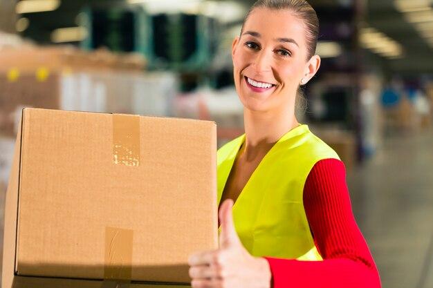 Trabalhadora com colete protetor detém pacote, parado no armazém da empresa de expedição de mercadorias