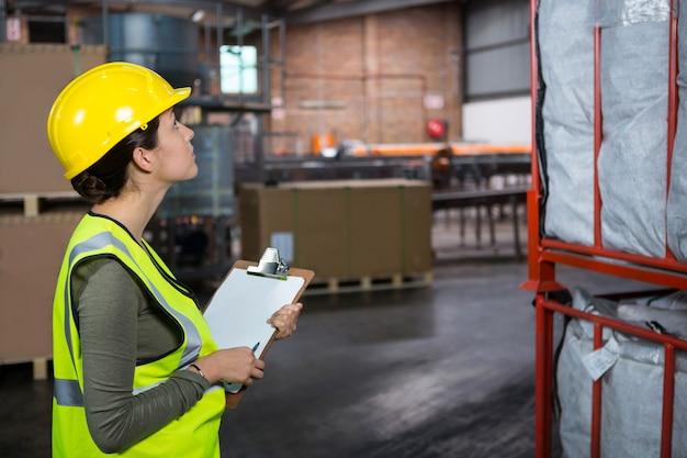 Trabalhadora confiante examinando produtos em depósito