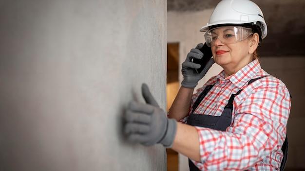 Trabalhadora da construção civil com capacete e smartphone