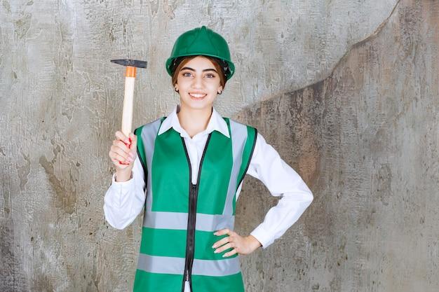 Trabalhadora da construção civil com capacete verde posando com um martelo