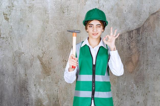 Trabalhadora da construção civil com capacete verde segurando um martelo e dando sinal de ok