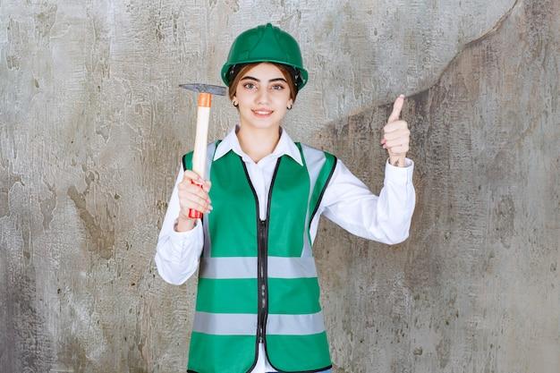 Trabalhadora da construção civil com capacete verde segurando um martelo e levantando os polegares