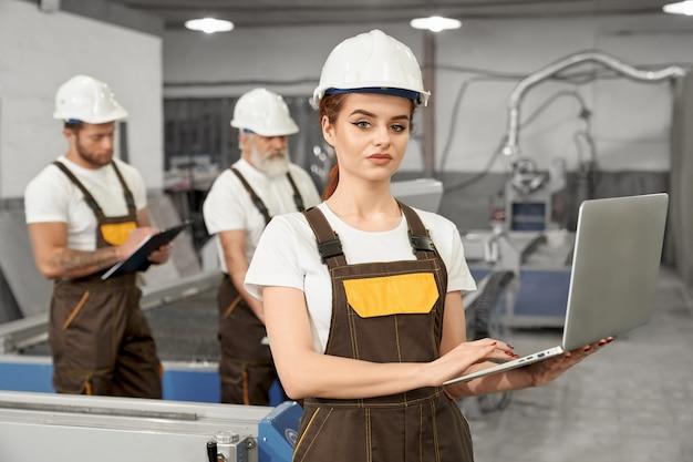 Trabalhadora da fábrica posando com notebook.