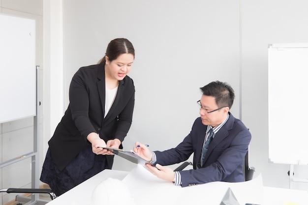 Trabalhadora de escritório apresentando documentos ao supervisor para reconhecimento e aprovação