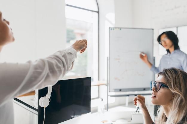 Trabalhadora de escritório com blusa branca apontando o dedo para a placa durante reunião com colegas