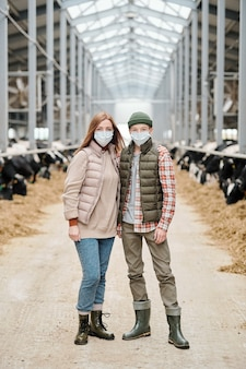 Trabalhadora de uma fazenda de animais e seu filho adolescente em trajes casuais e máscaras protetoras em pé contra o longo corredor entre os piquetes