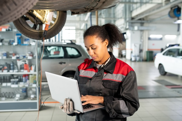 Trabalhadora de uma oficina mecânica de uniforme usando laptop na oficina para procurar dados em fontes online, anotar novos pedidos ou consultar clientes