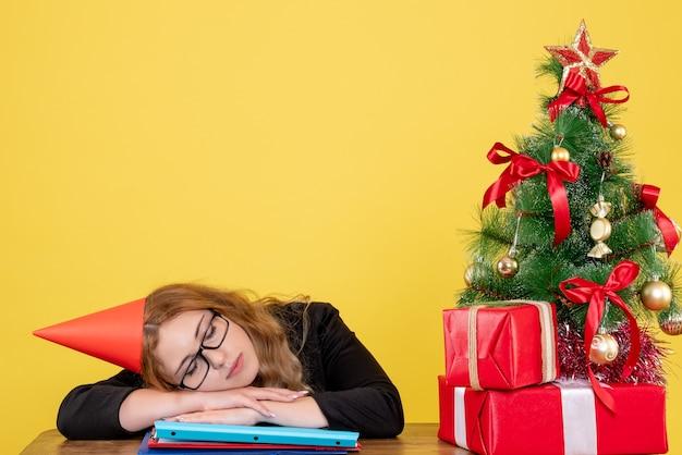 Trabalhadora dormindo em seu local de trabalho em amarelo