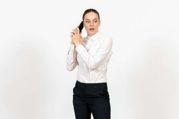Trabalhadora em elegante blusa branca falando no telefone assustada no branco