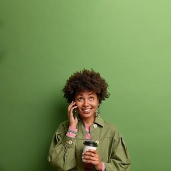 Trabalhadora étnica feliz trabalha produtivamente com um café energético, conversa ao telefone com um colega, olha para cima com um sorriso cheio de dentes, segura um copo descartável, espera alguém na reunião