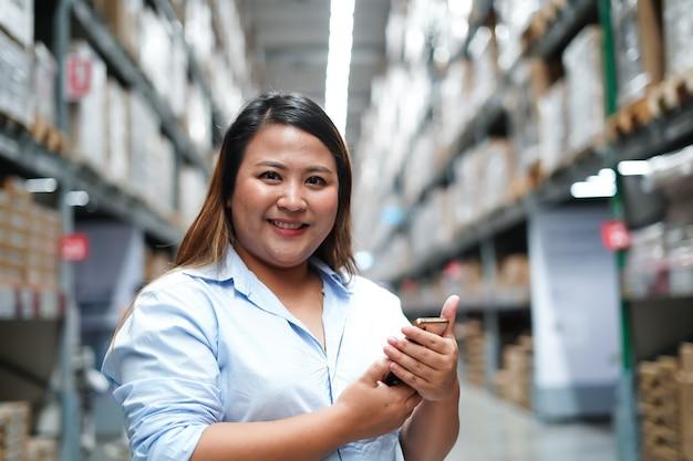 Trabalhadora inspecionando caixa de produtos enquanto trabalhava em um grande armazém