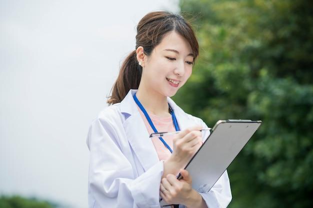 Trabalhadora médica asiática com ficha médica e caneta
