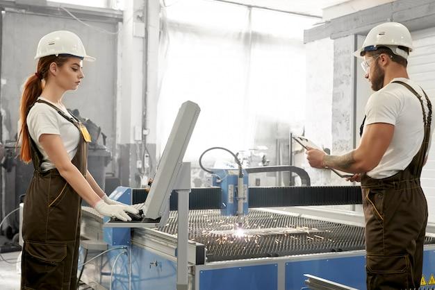 Trabalhadora, olhando para o computador enquanto macho mantendo a pasta