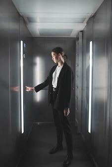 Trabalhadora pressionando o botão no elevador.