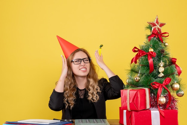 Trabalhadora sentada atrás de seu local de trabalho em amarelo