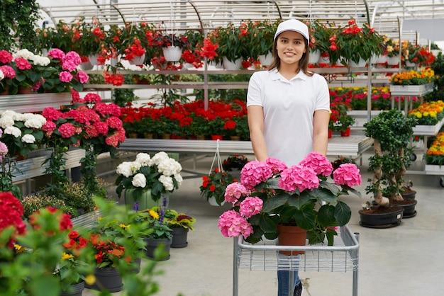Trabalhadora sorridente com flores na estufa