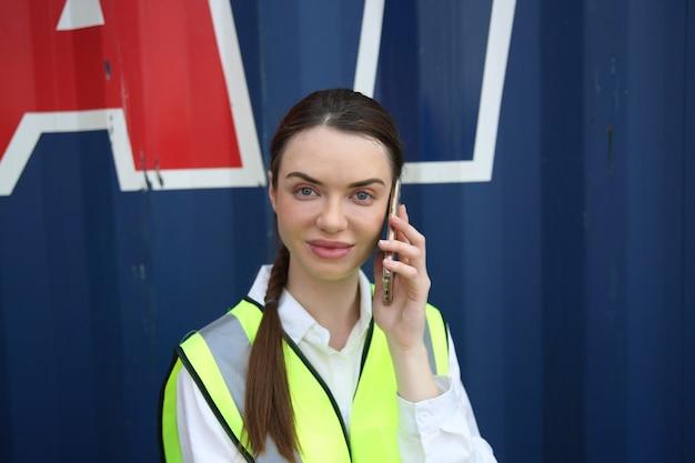 Trabalhadora sorridente, falando ao telefone no canteiro de obras.