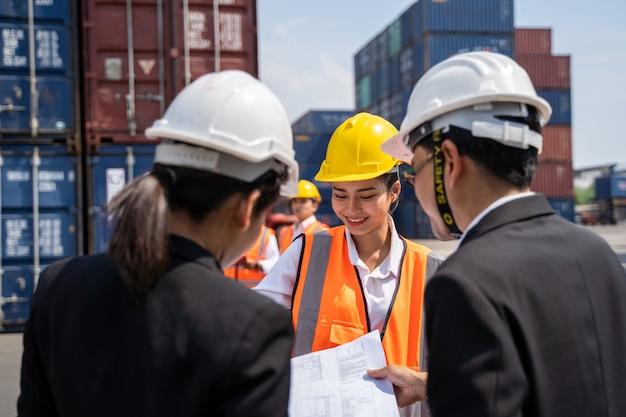 Trabalhadora trabalhando com foreman, segurando um capacete amarelo para controlar o carregamento e verificar a qualidade dos contêineres do navio de carga para importação e exportação no estaleiro ou porto