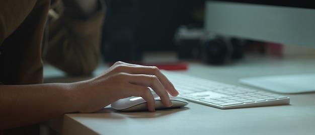 Trabalhadora, trabalhando com o dispositivo do computador na mesa de escritório branca com câmera e outros suprimentos