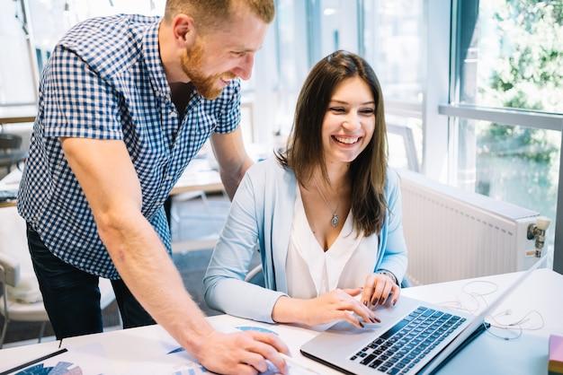 Trabalhadores alegres no computador portátil