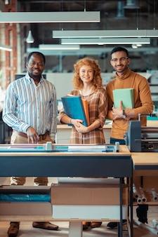 Trabalhadores alegres. trabalhadores alegres e bonitos de uma editora sorrindo enquanto seguram livros