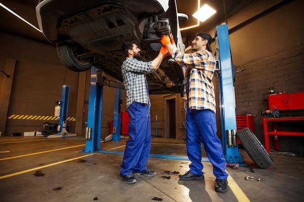 Trabalhadores alegres trocando o pneu de um carro levantado na estação de serviço, com vista para a vista