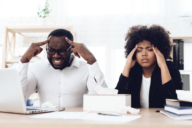 Trabalhadores americanos do co com a gripe que senta-se na tabela no trabalho.
