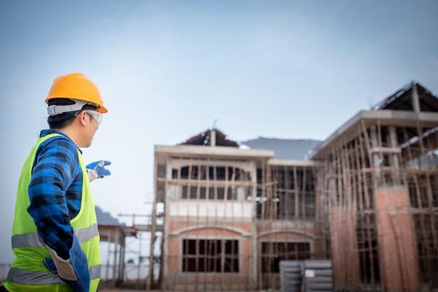Trabalhadores asiáticos da construção civil vêem a construção de uma casa grande ou de um canteiro de obras que está prestes a ser construído.