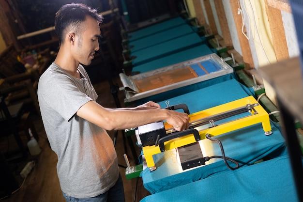 Trabalhadores asiáticos do sexo masculino seguram cuidadosamente o aquecedor para secar a tinta de impressão da tela após a impressão