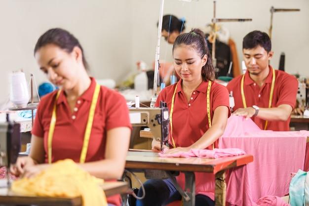 Trabalhadores asiáticos em costura de fábrica de roupas com costura industrial