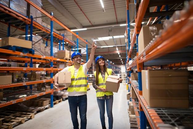 Trabalhadores carregando caixas e realocando pacotes para a posição apropriada na prateleira para uma boa organização no centro de armazenamento
