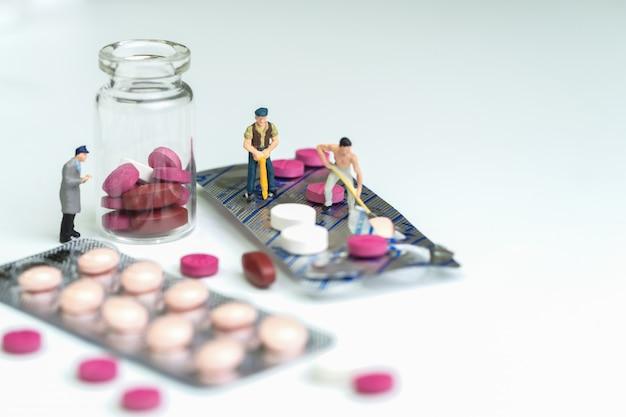 Trabalhadores cavando medicina comprimidos em fundo branco