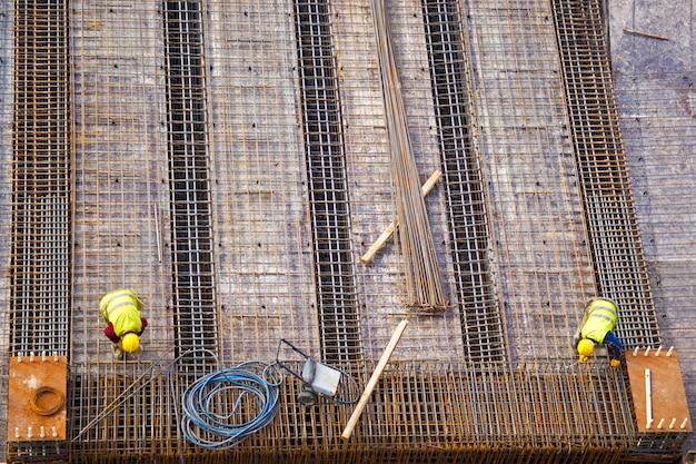 Trabalhadores colocando a estrutura metálica de uma construção