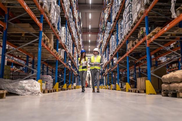 Trabalhadores com capacetes e jaquetas reflexivas caminhando pelo grande corredor do armazém verificando as condições das mercadorias