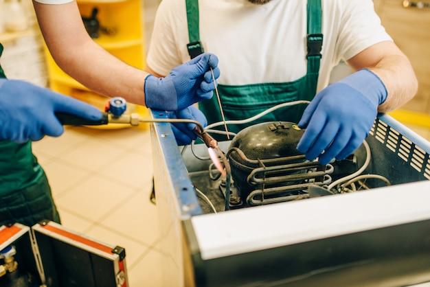 Trabalhadores com queimador consertam geladeira em casa