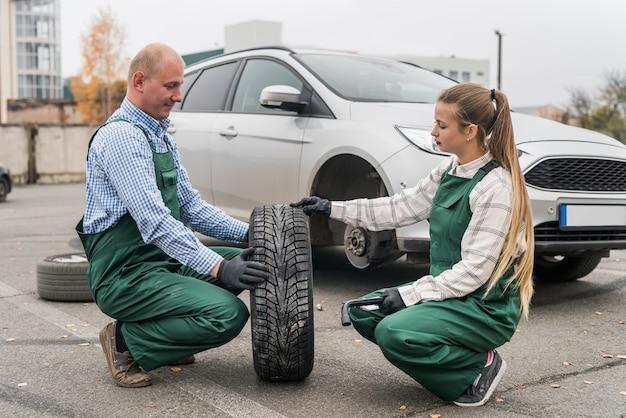 Trabalhadores com roda sobressalente de um carro na beira da estrada