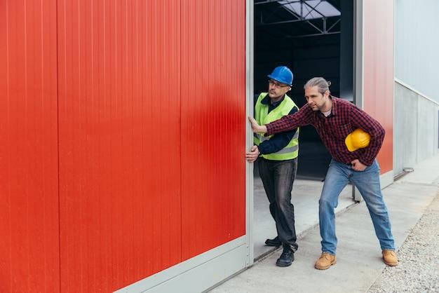 Trabalhadores da construção civil abrindo a porta do hangar