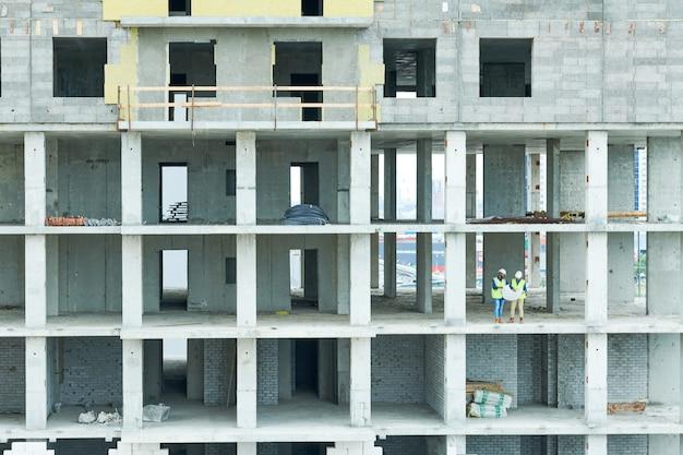 Trabalhadores da construção civil analisando o plano do projeto