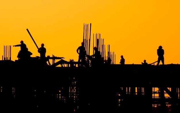 Trabalhadores da construção civil ao pôr do sol.