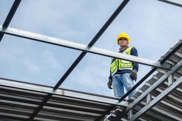 Trabalhadores da construção civil asiáticos estão na estrutura do telhado do edifício na área de construção. indo instalar o telhado
