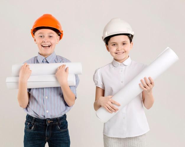Trabalhadores da construção civil bonitos segurando projetos