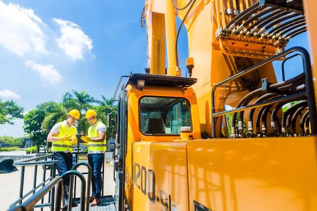 Trabalhadores da construção civil discutindo plantas