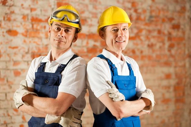 Trabalhadores da construção civil em pé com os braços cruzados