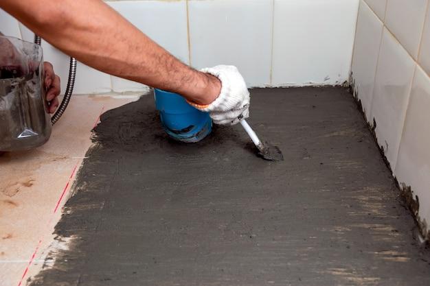 Trabalhadores da construção civil escovam cimento impermeabilizante no piso de cerâmica do banheiro.