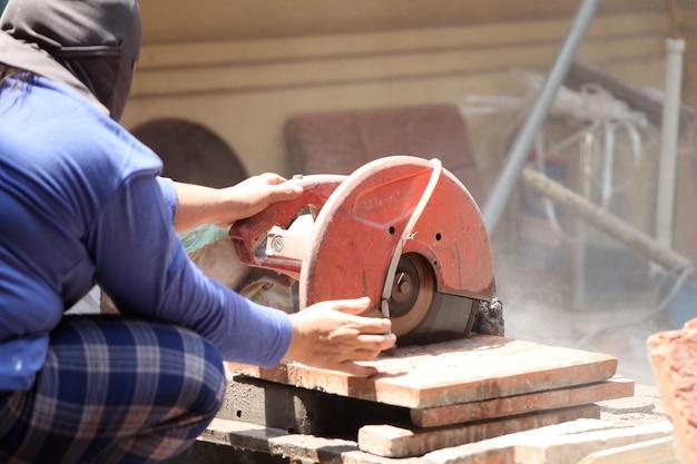 Trabalhadores da construção civil estão cortando ladrilhos