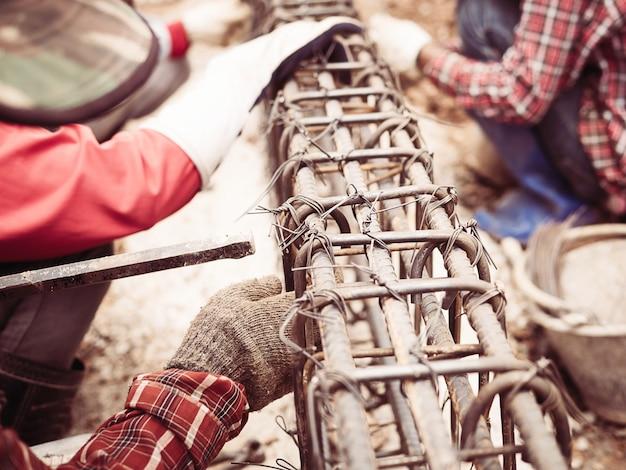 Trabalhadores da construção civil estão instalando hastes de aço em vigas de concreto armado