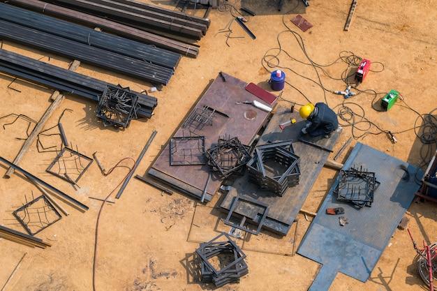 Trabalhadores da construção civil estão soldando aço a partir da vista superior.