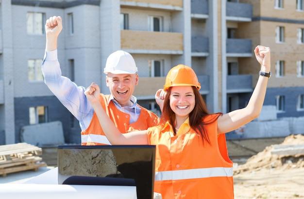 Trabalhadores da construção civil femininos e masculinos de sucesso com um laptop e desenhos